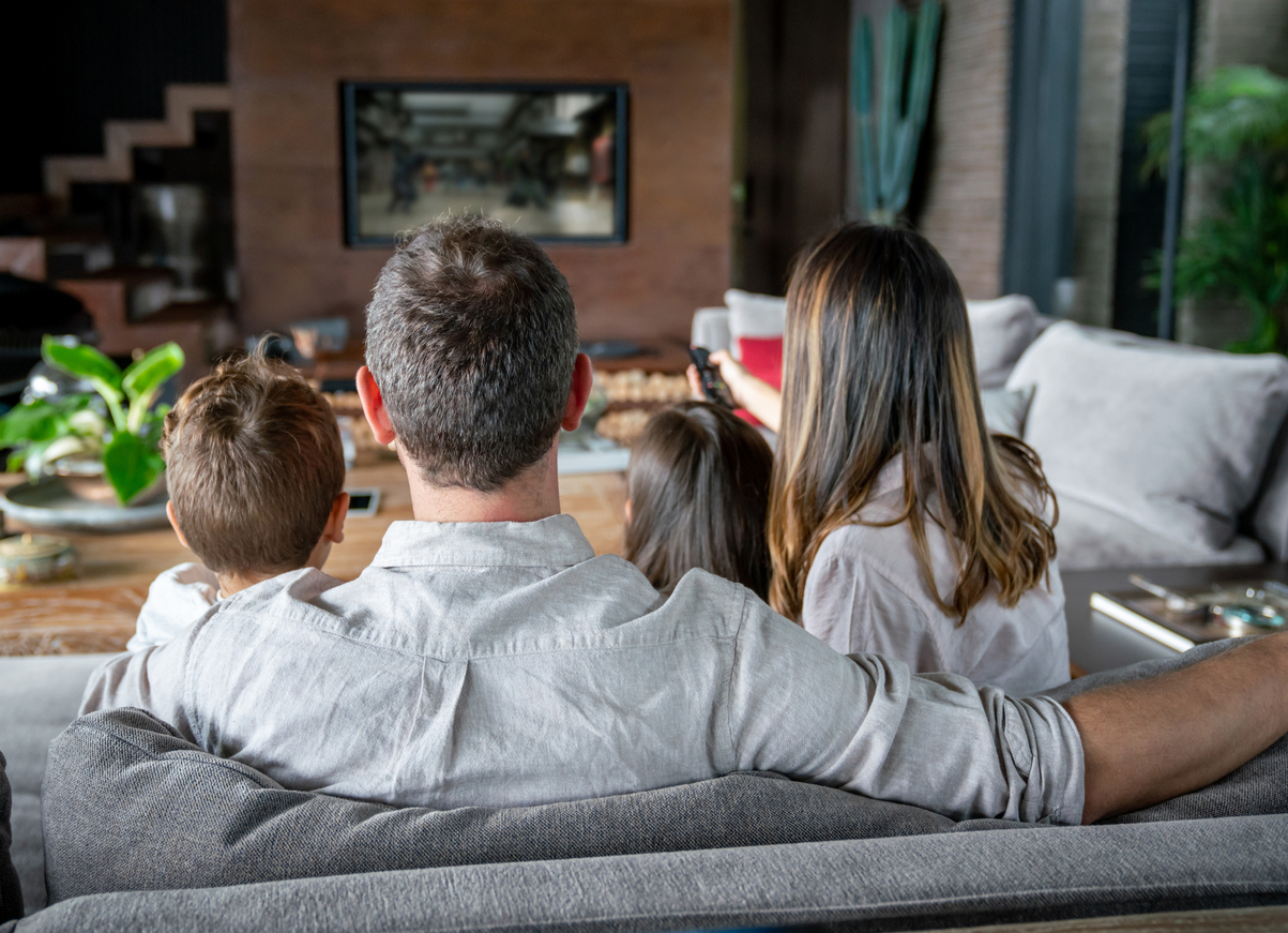 Backview of latin american family at home watching TV while mom changes channels